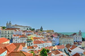 White houses with terracotta roofs under a blue sky in Lisbon